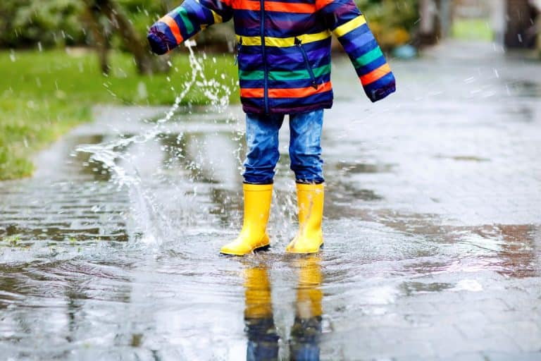 child jumping in puddles on a rainy day in Dorset