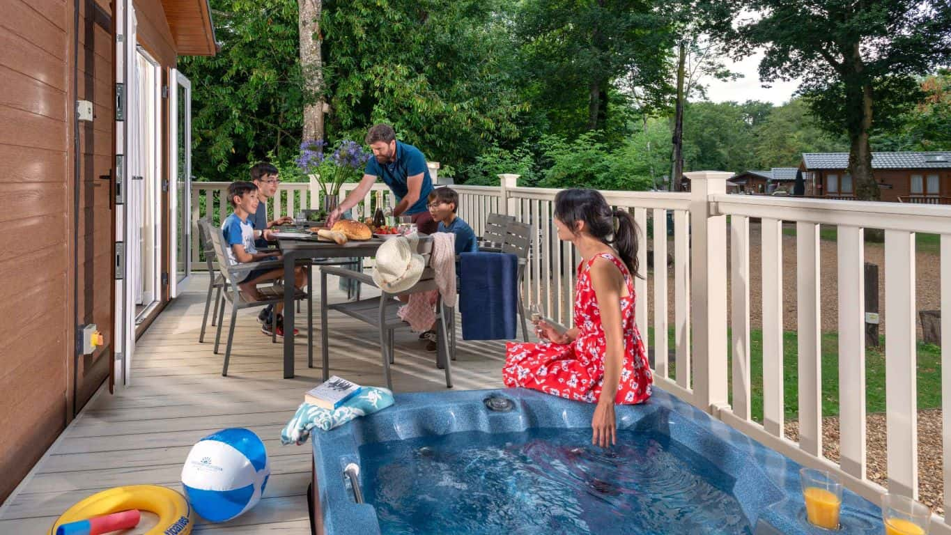Shorefield Family-enjoying-meal-on-decking-of-hot-tub-lodge