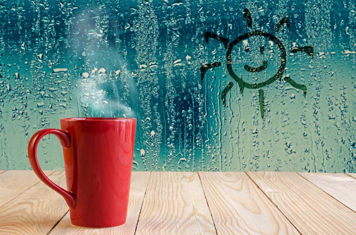red mug next to a rain splattered window on a rainy day in Cornwall